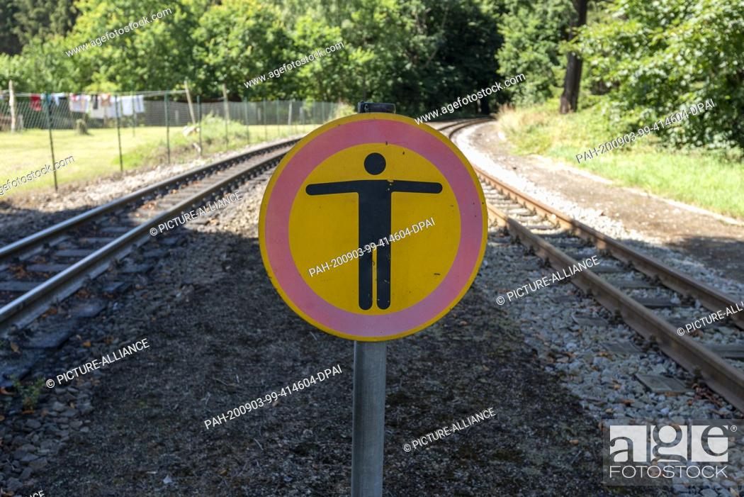 Stock Photo: 03 August 2020, Mecklenburg-Western Pomerania, Garftitz: At the Garftitz railway station, a sign warns against stepping on the tracks.