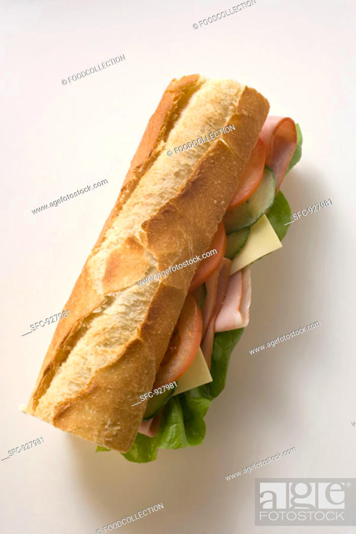 Stock Photo: Baguette with ham, cheese, tomato, cucumber and lettuce.