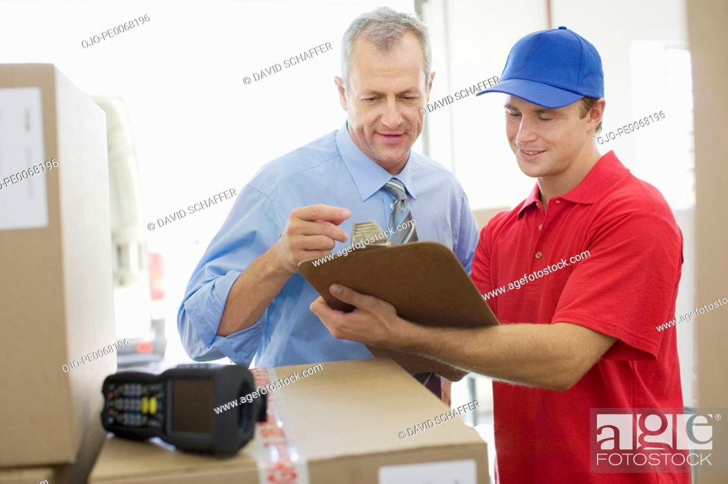 Stock Photo: Businessman talking with delivery man in warehouse.