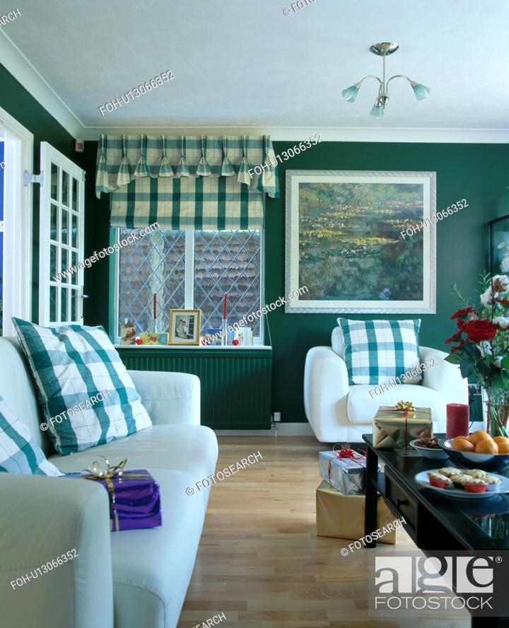 Green checked cushions on white sofa and armchair in dark ...