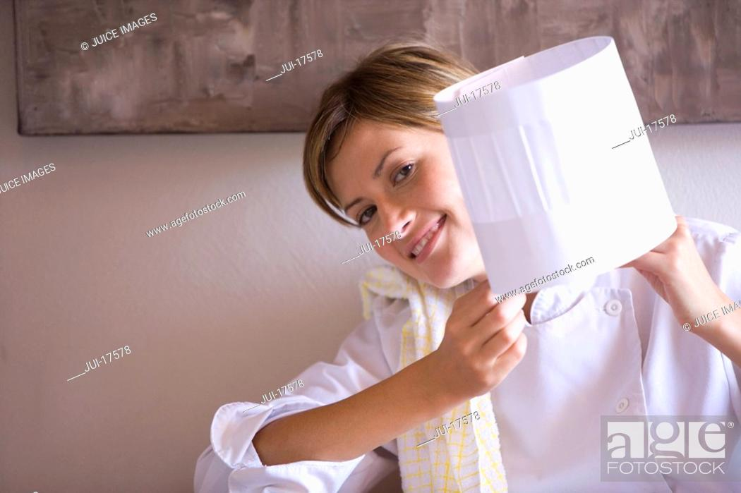 Stock Photo: Female chef showing off hat.