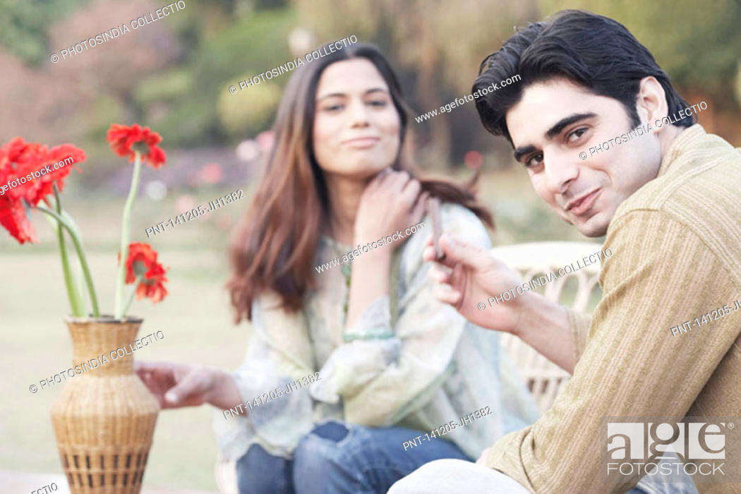 Stock Photo: Portrait of a young couple sitting in a garden.