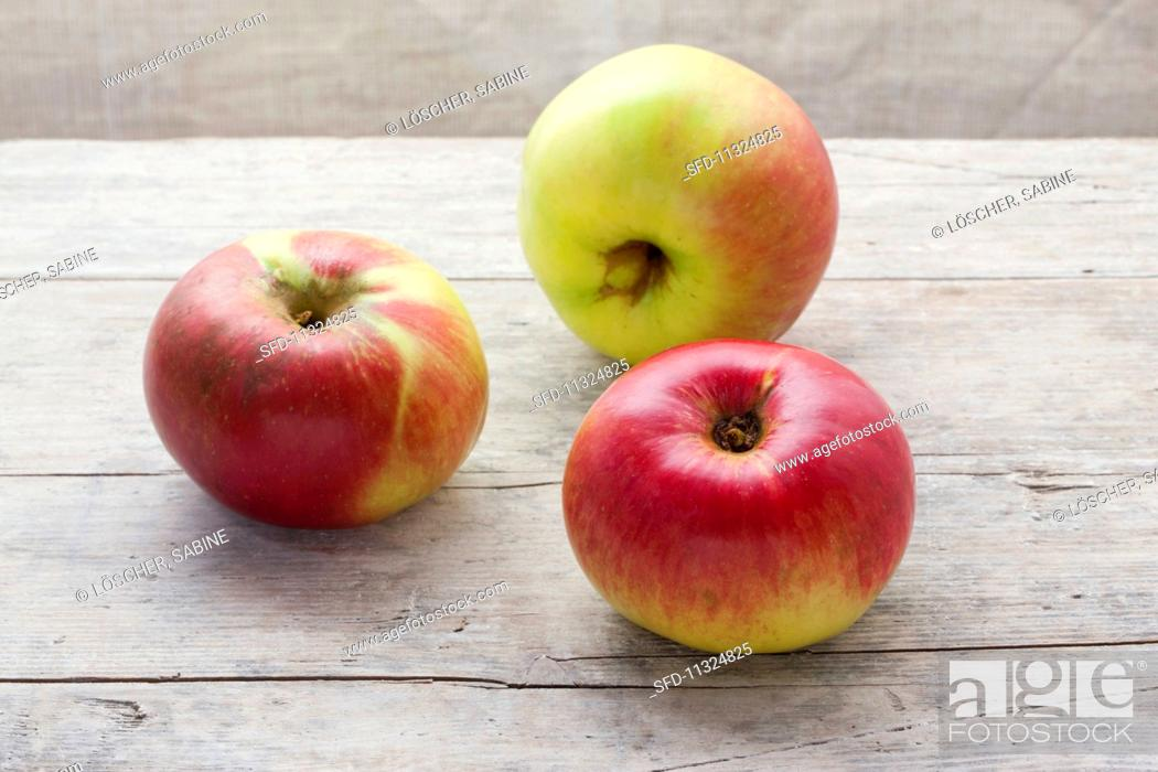 Stock Photo: Three organic Brettacher apples on a wooden surface.