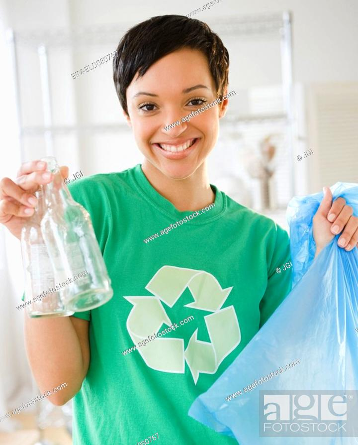 Stock Photo: Mixed race woman recycling bottles.