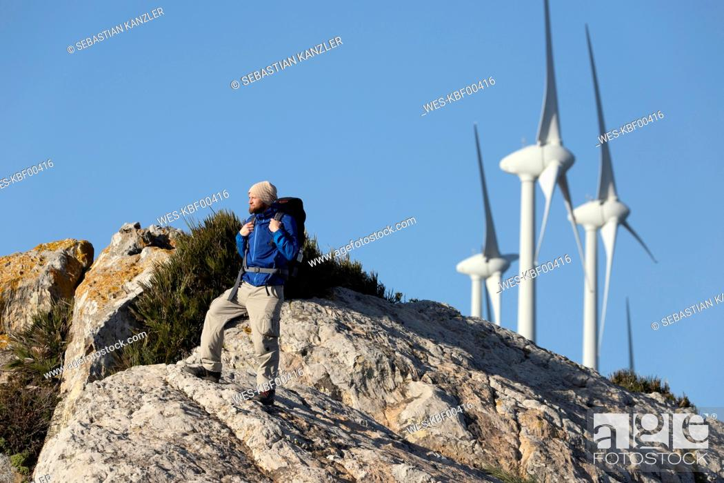 Stock Photo: Spain, Andalusia, Tarifa, man on a hiking trip standing on rock with wind turbines in background.