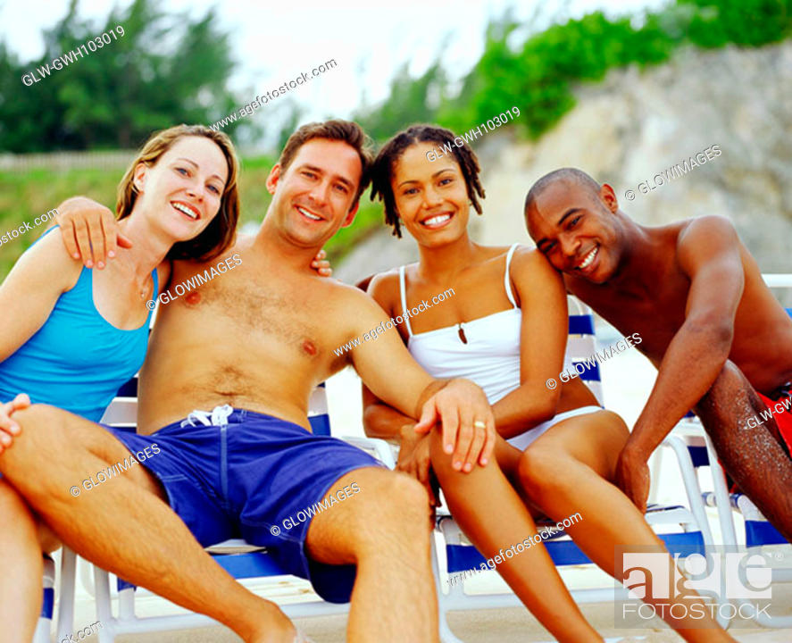 Stock Photo: Portrait of two young couples sitting on lounge chairs and smiling, Bermuda.