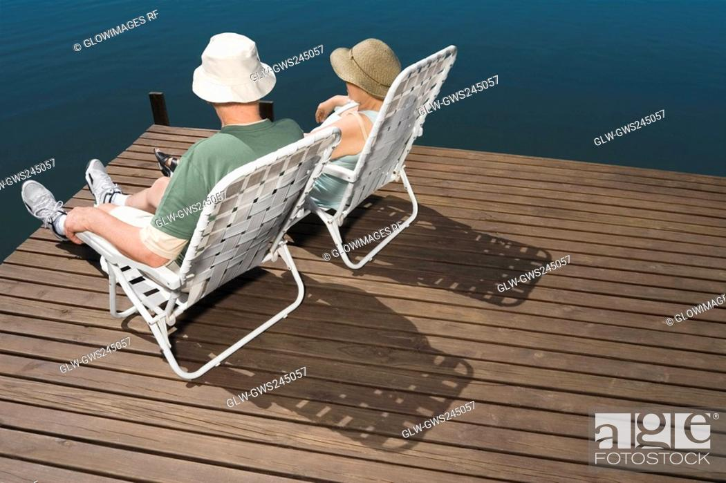 Stock Photo: Rear view of a senior couple sitting on chairs at the lakeside.
