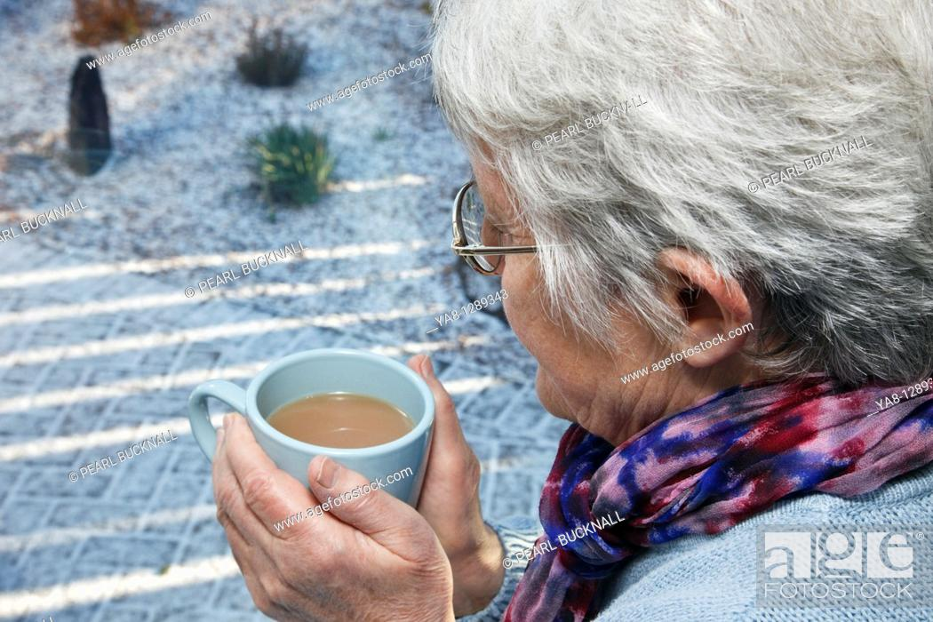 Stock Photo: UK, Europe Senior woman holding a warm drink looking out of the window on a cold snowy day in winter.