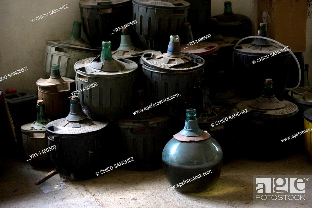 Stock Photo: Old demijohns sit in a storage room in a house of El Gastor village in the Sierra de Grazalema Natural Park, Cadiz province, Andalusia, Spain, april 26, 2011.