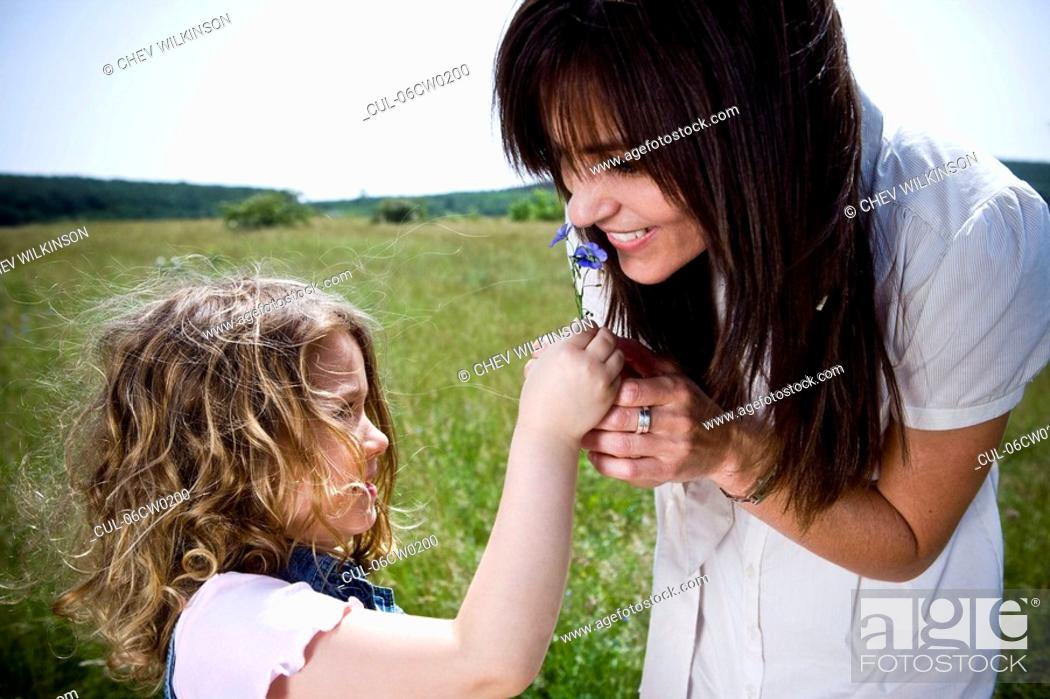 Stock Photo: Woman smelling flower with daughter.