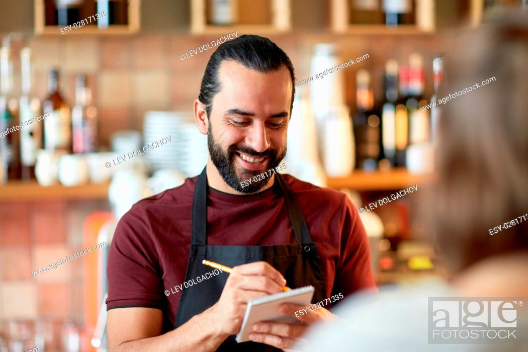 Stock Photo: small business, people and service concept - happy man or waiter with notebook and pencil serving customer at coffee shop or bar.