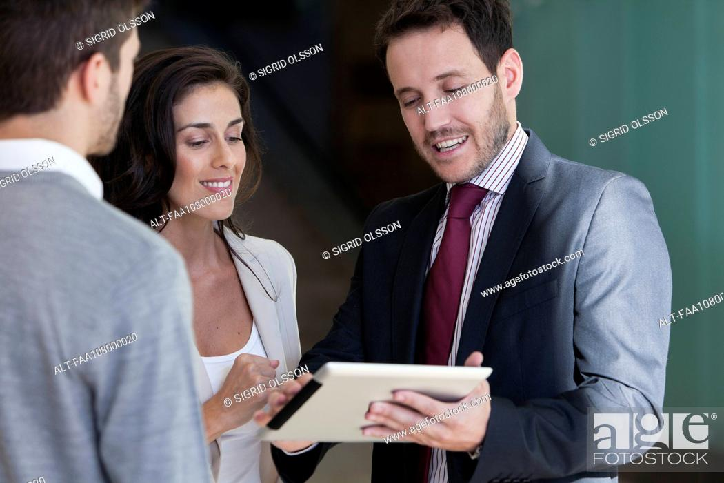 Stock Photo: Business associates looking at proposal on digital tablet together.