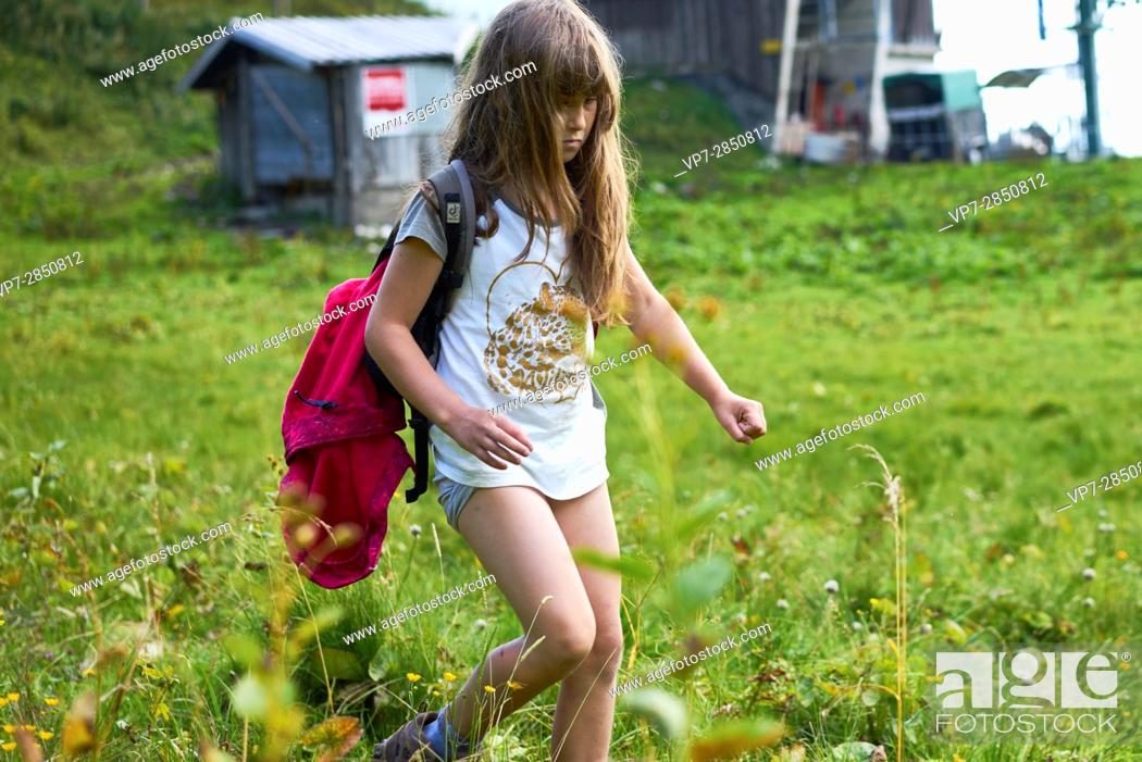 Stock Photo: Young female child walking over green grass during hiking adventure in nature, Brauneck, Bavaria, Germany.