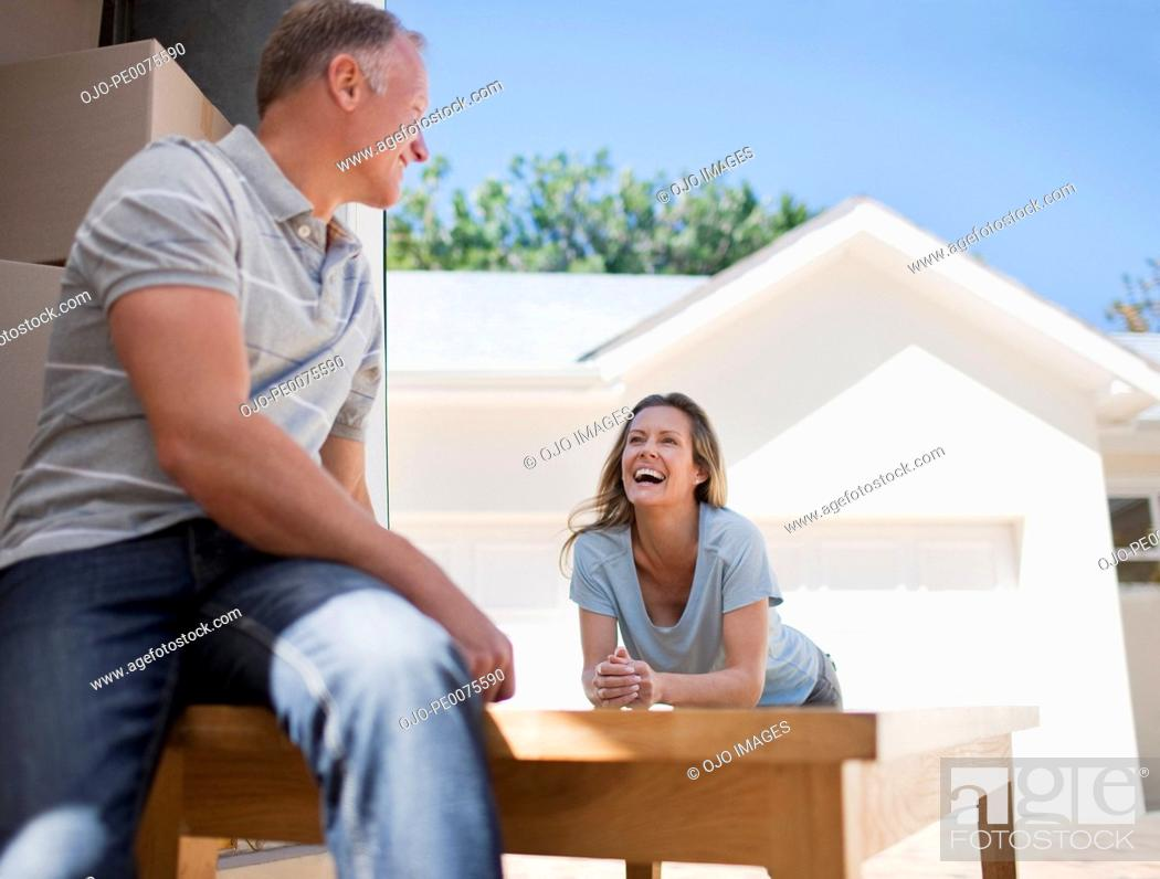 Stock Photo: Couple moving table into new house.