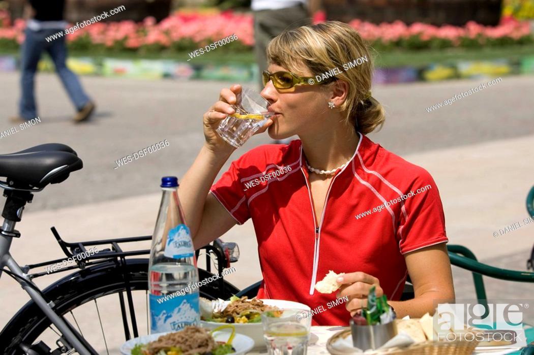 Stock Photo: Italy, Trento, Arco, Woman with mountainbike drinking water.