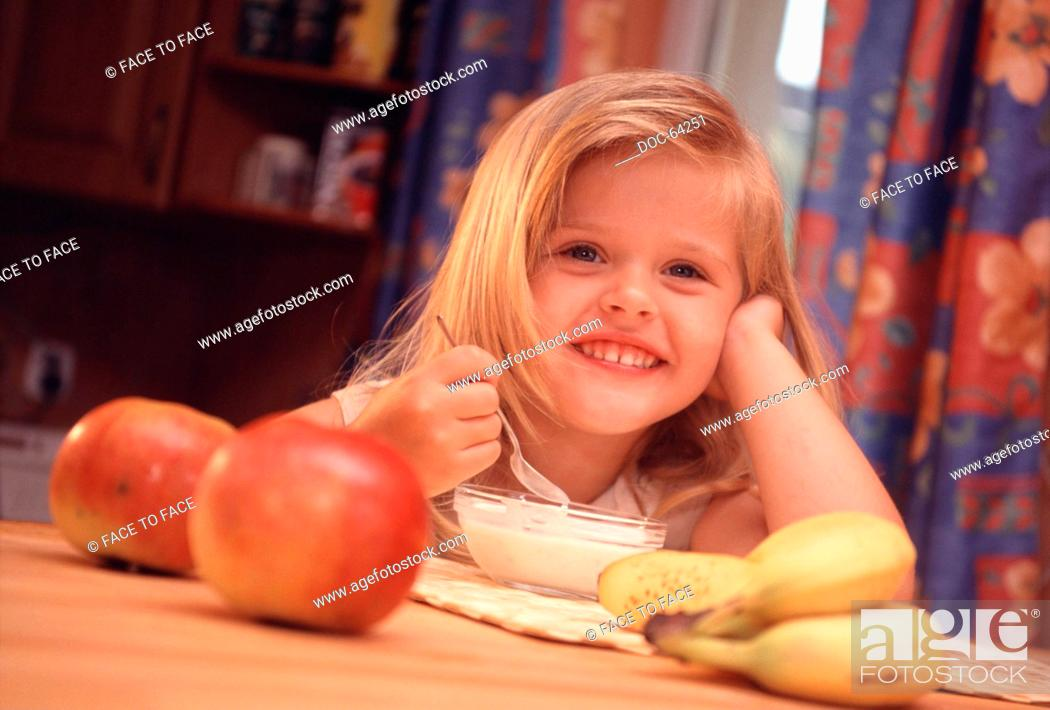 Stock Photo: Small fair Pre-Teen girl is at the table mitt fresh fruit and eats a yogurt.