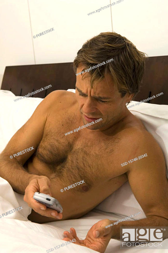 Stock Photo: Close-up of a young man operating a mobile phone in the bed.