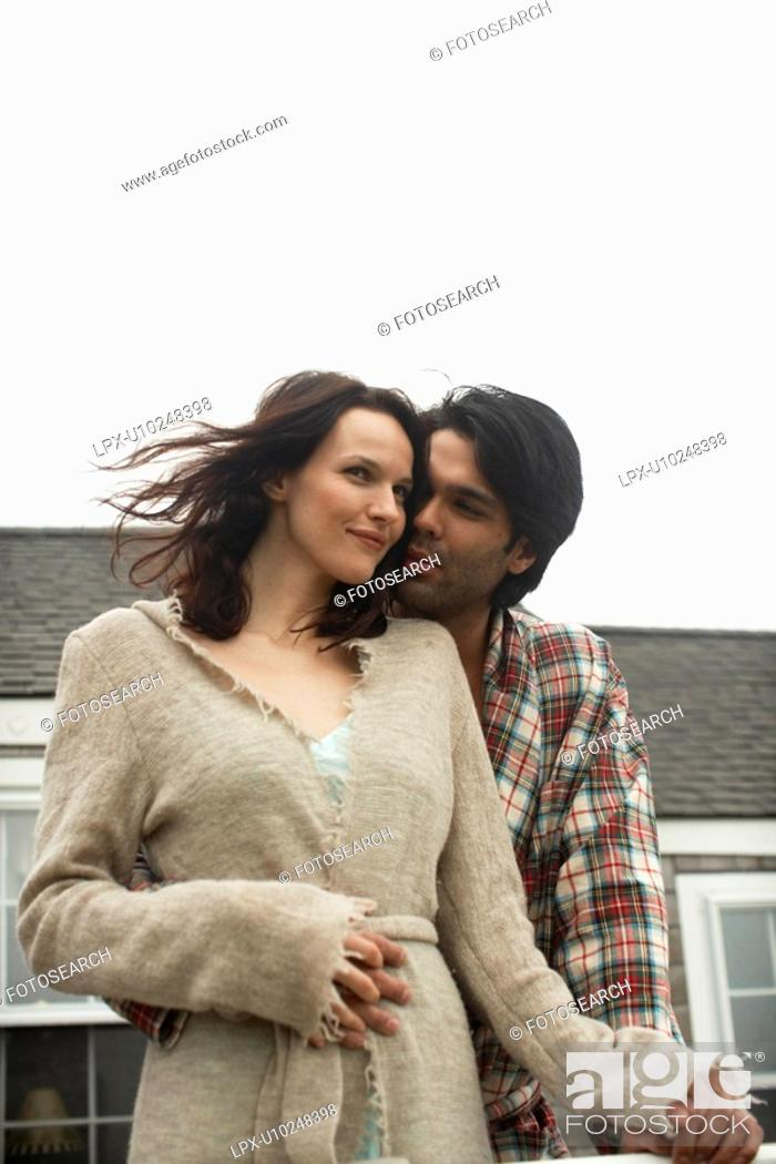Stock Photo: Young couple outside house low angle view.