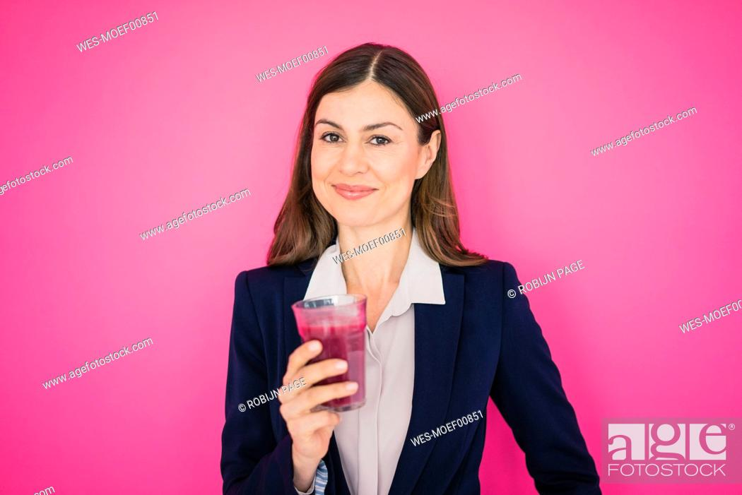 Imagen: Portrait of smiling businesswoman in front of pink wall holding glass of juice.