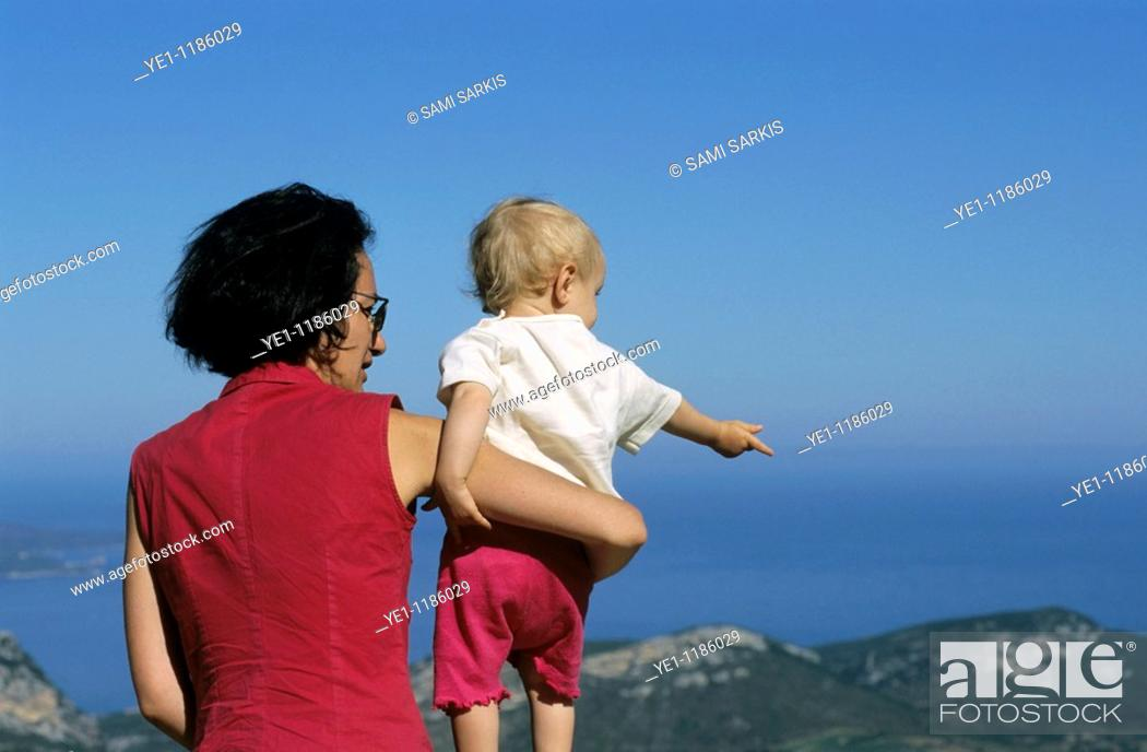 Stock Photo: Mother holding her baby girl while looking at the sea view.
