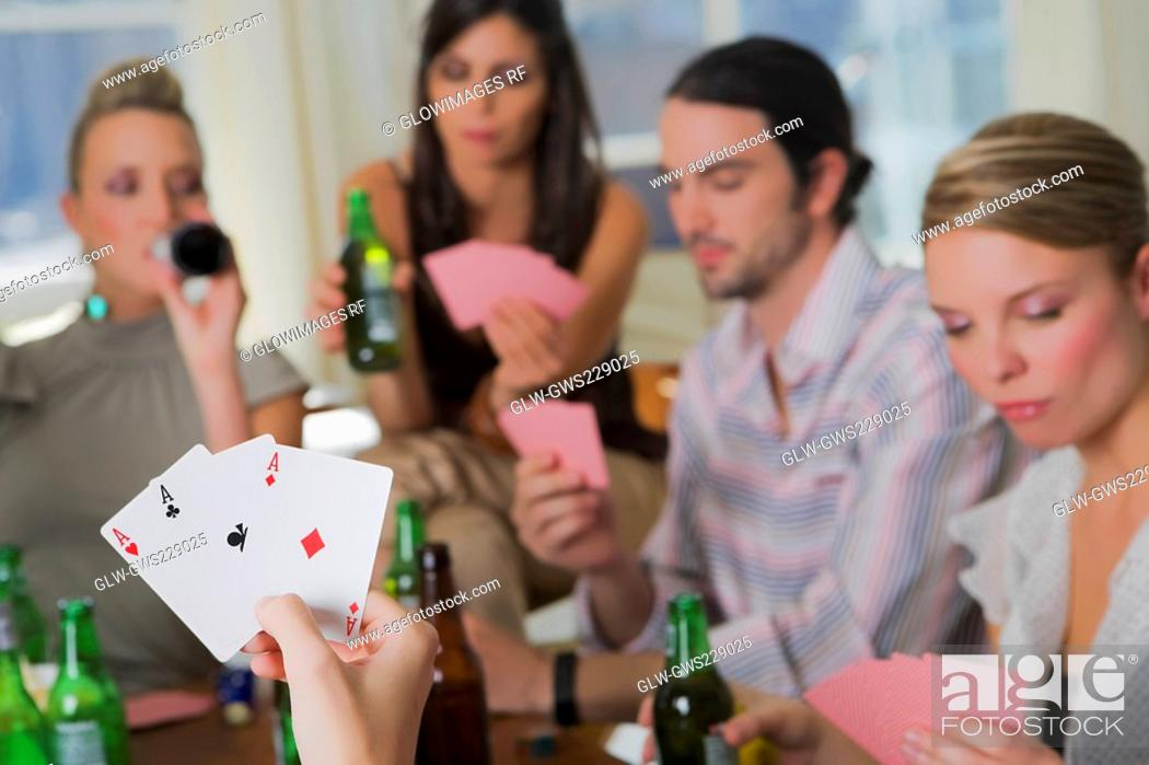 Stock Photo: Young man with her friends playing cards.