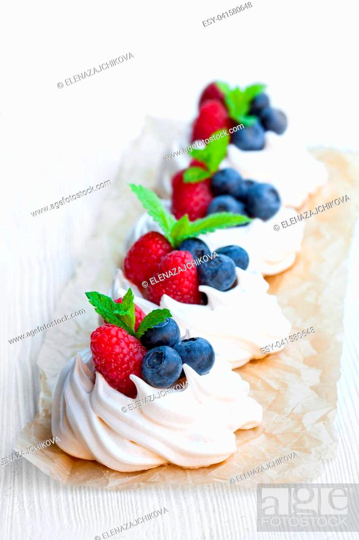Stock Photo: Mini Pavlova meringue cakes with berries and mint on white wooden background.