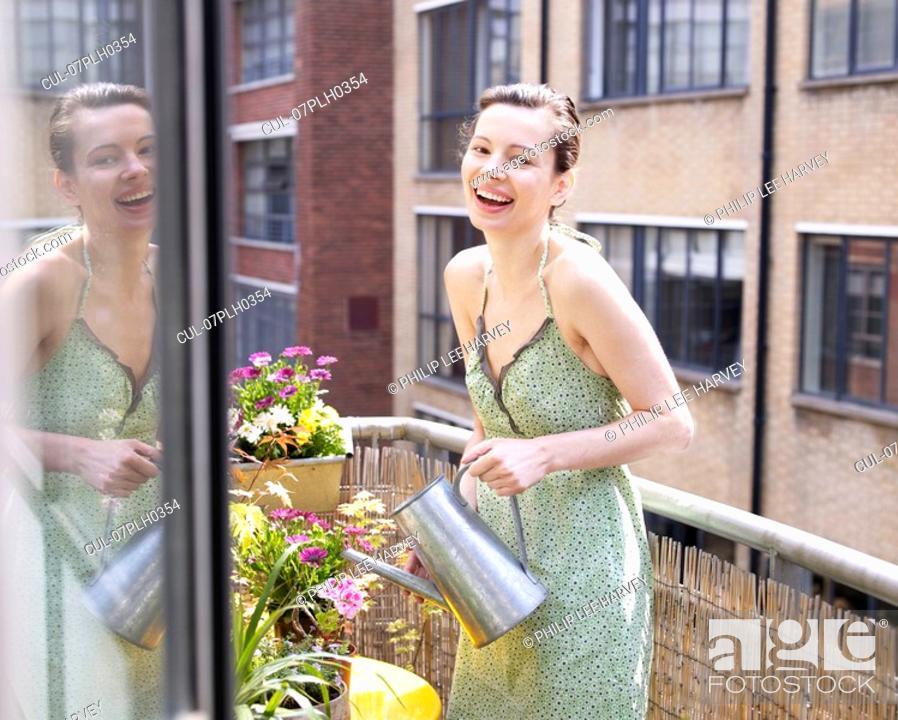 Stock Photo: Woman on balcony watering flowers.