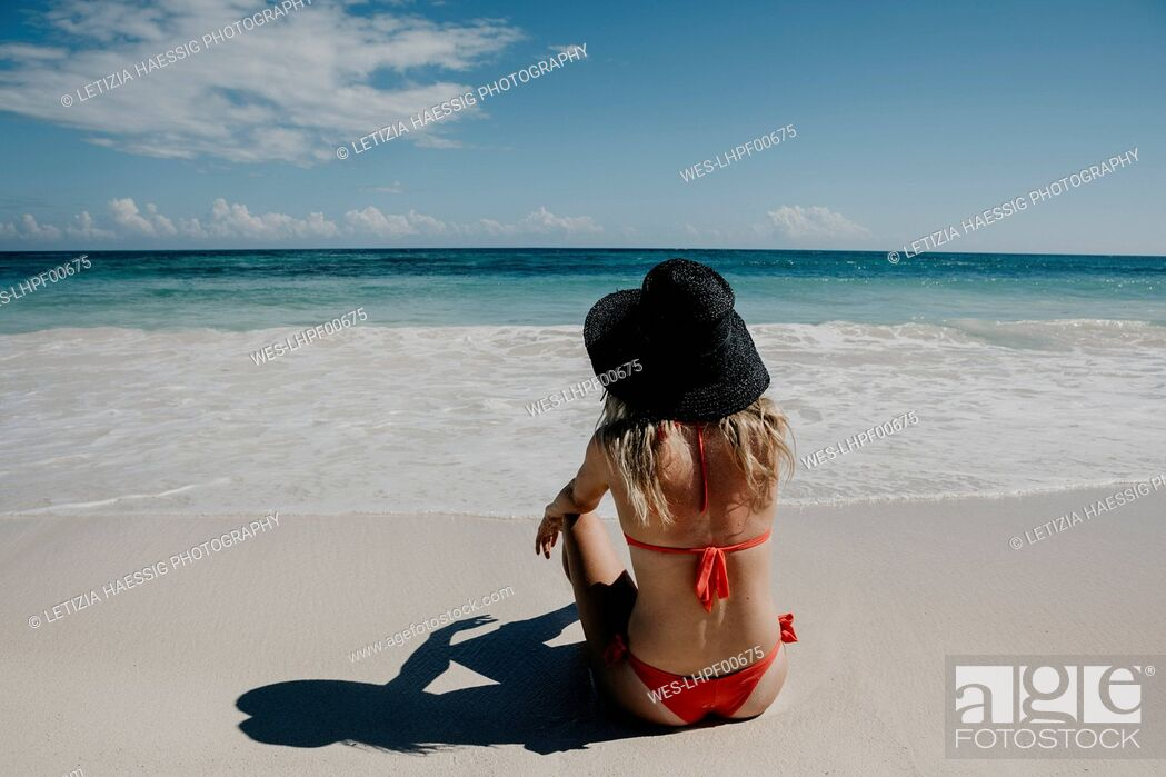 Stock Photo: Mexico, Quintana Roo, Tulum, young woman with hat lying on the beach.