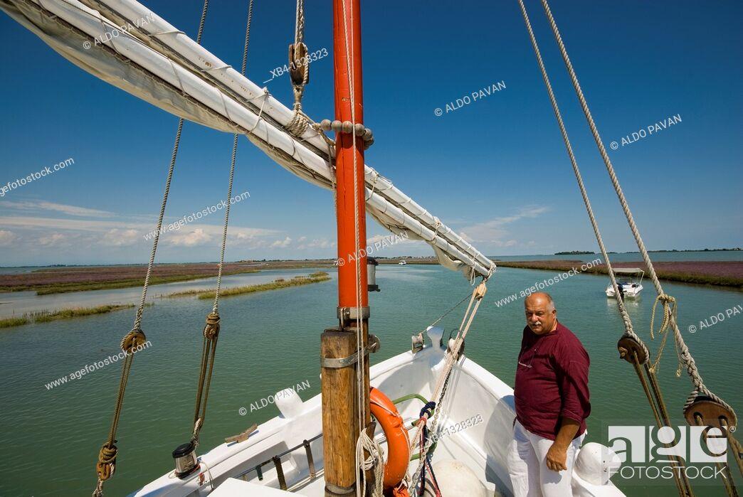 Stock Photo: Italy, Venice, cruising the lagune with Eolo, a traditional Venetian fishing boat called 'bragozzo'.