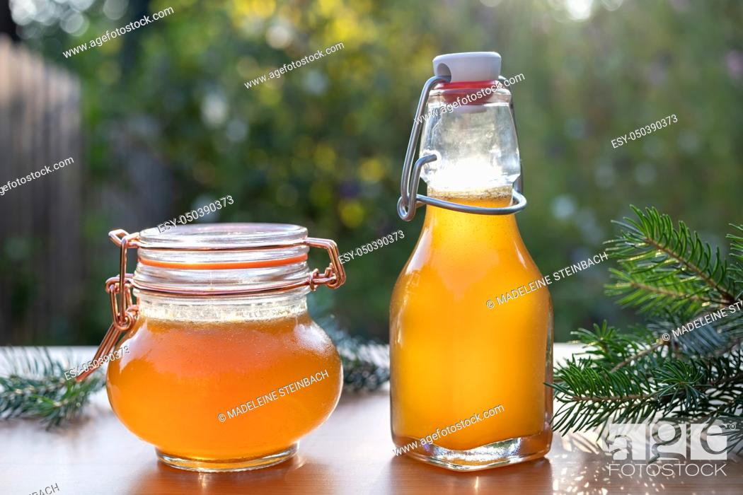 Stock Photo: A bottle and a jar of homemade herbal syrup against cough made from young spruce tips, photographed in a garden.