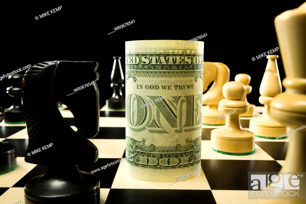 Stock Photo: rolled currency on a chess board.