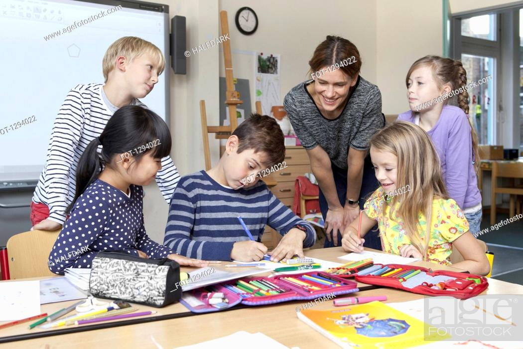 Stock Photo: Teacher with students in classroom.
