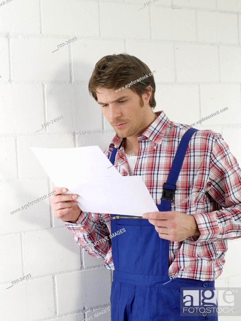 Stock Photo: Mann wearing work wear holding contruction plans.