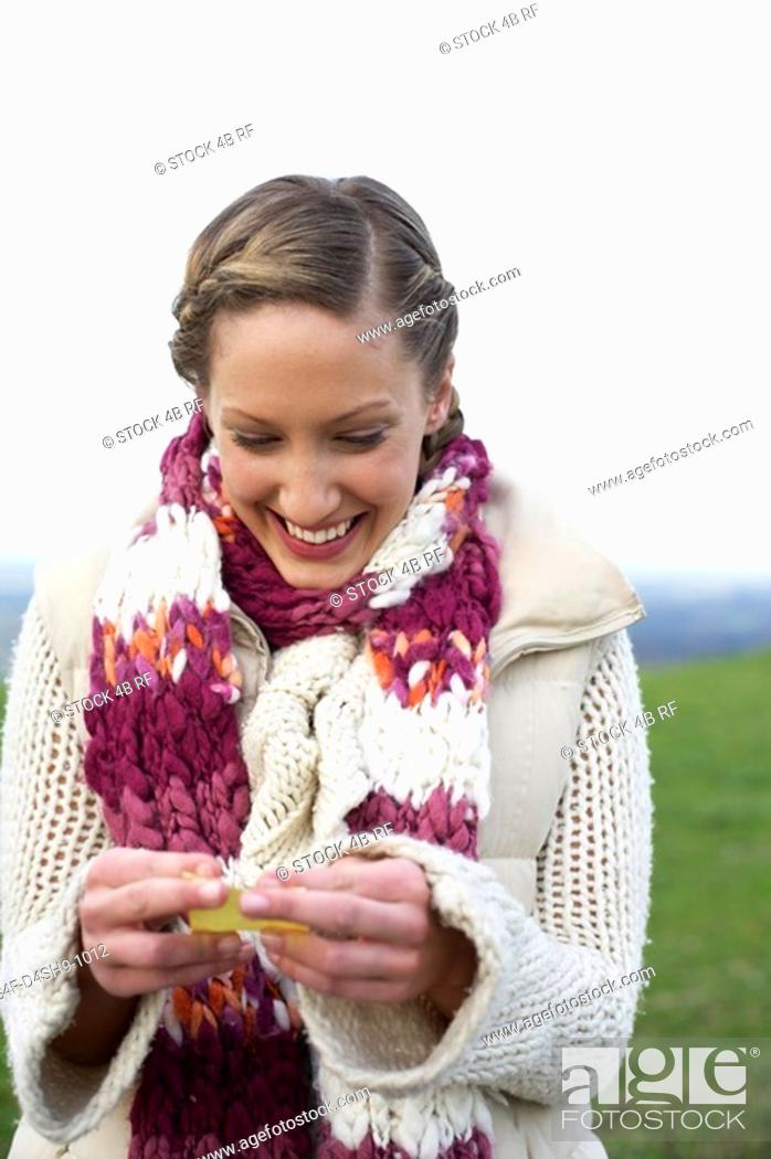 Stock Photo: Young woman with scarf and cardigan is holding a little note in her hands, close-up.
