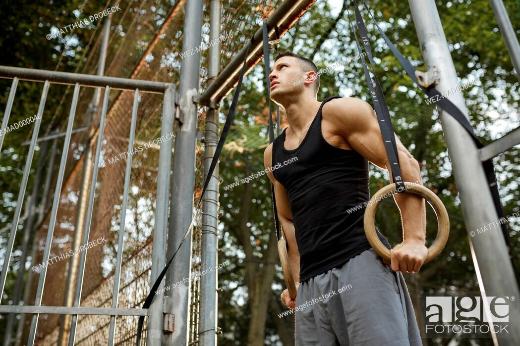 Imagen: Muscly young man training on gymnastic rings.