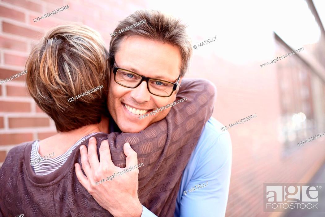 Stock Photo: Couple hugging on city street.