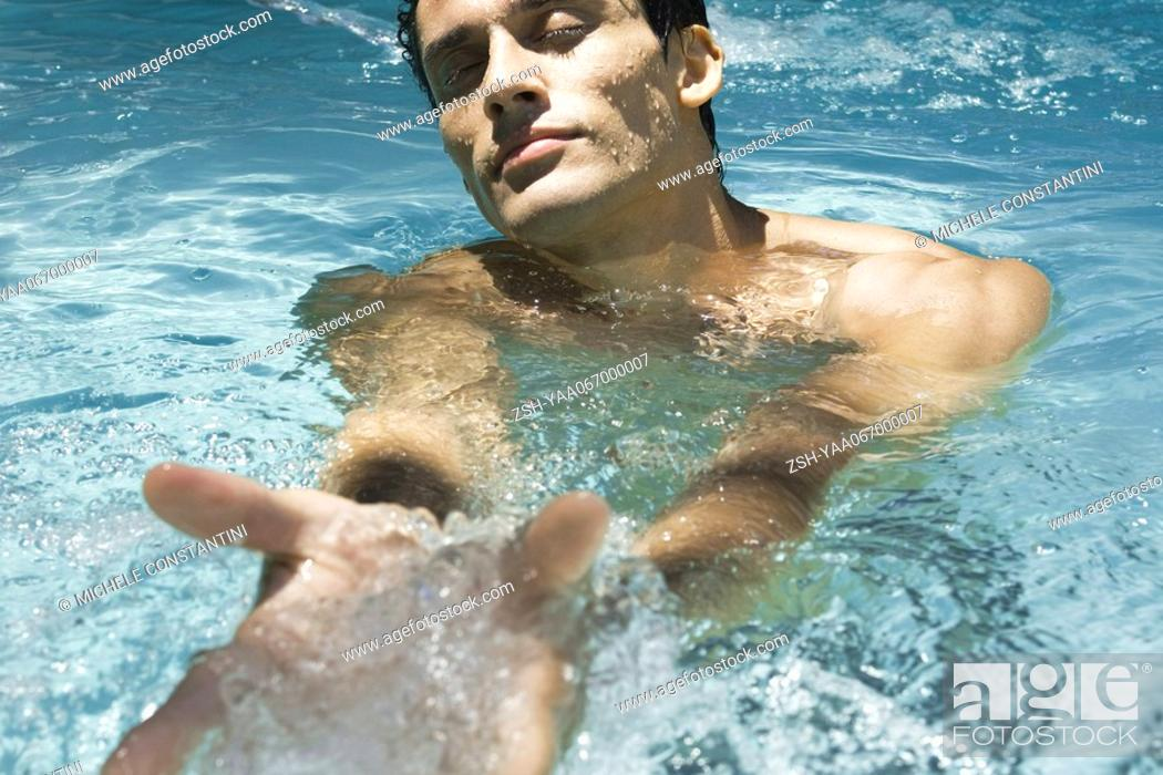 Stock Photo: Man in swimming pool with eyes closed, scooping water with hands.