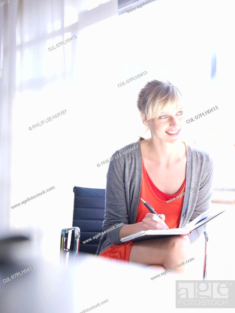Stock Photo: Woman writing at home office.