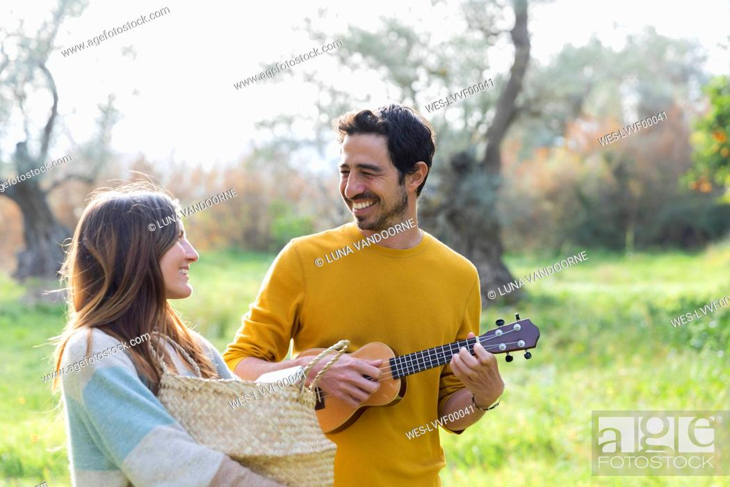 Imagen: Woman carrying wicker basket while happy man playing guitar at countryside.