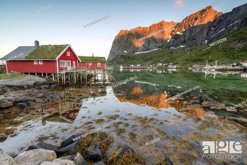 Stock Photo: Fishing village and peaks reflected in water under midnight sun Reine Nordland county Lofoten Islands Northern Norway Europe.