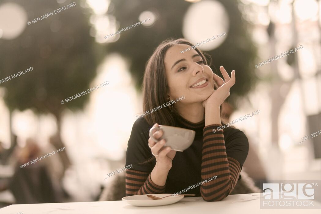 Stock Photo: portrait of woman holding coffee cup while enjoying break at table in café, in Munich, Germany.