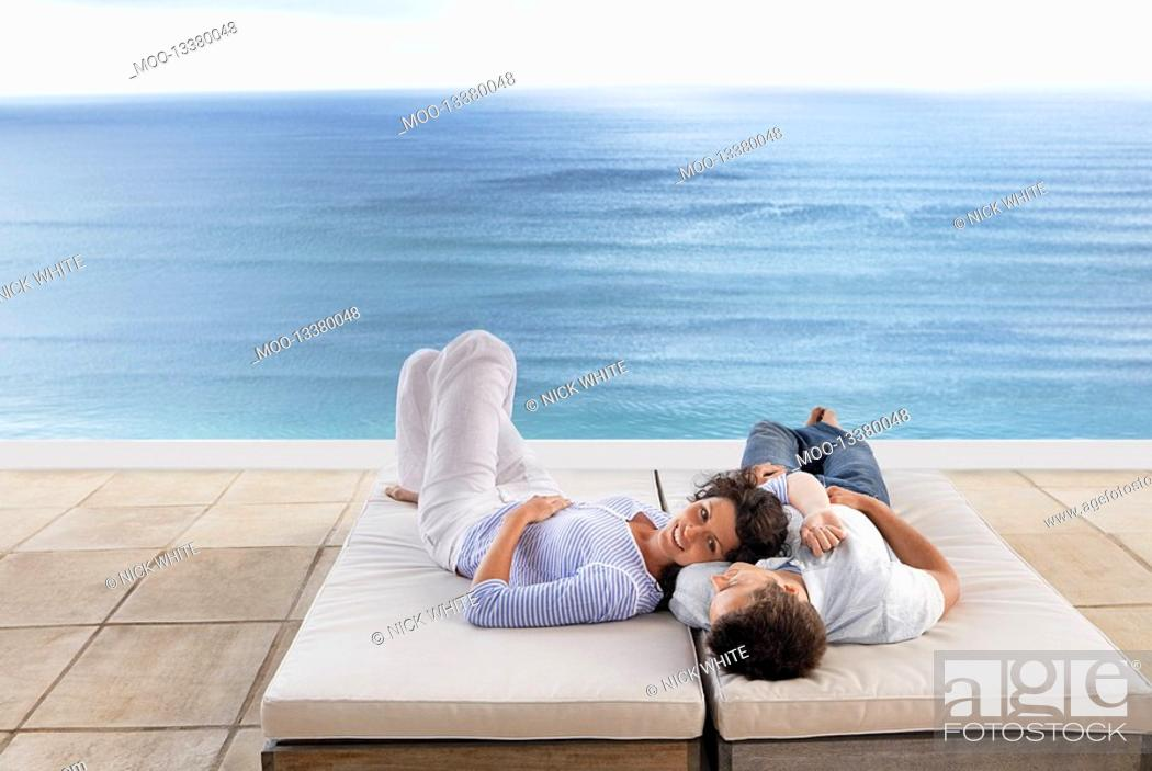 Stock Photo: Couple lying down on sun beds on terrace overlooking sea elevated view.