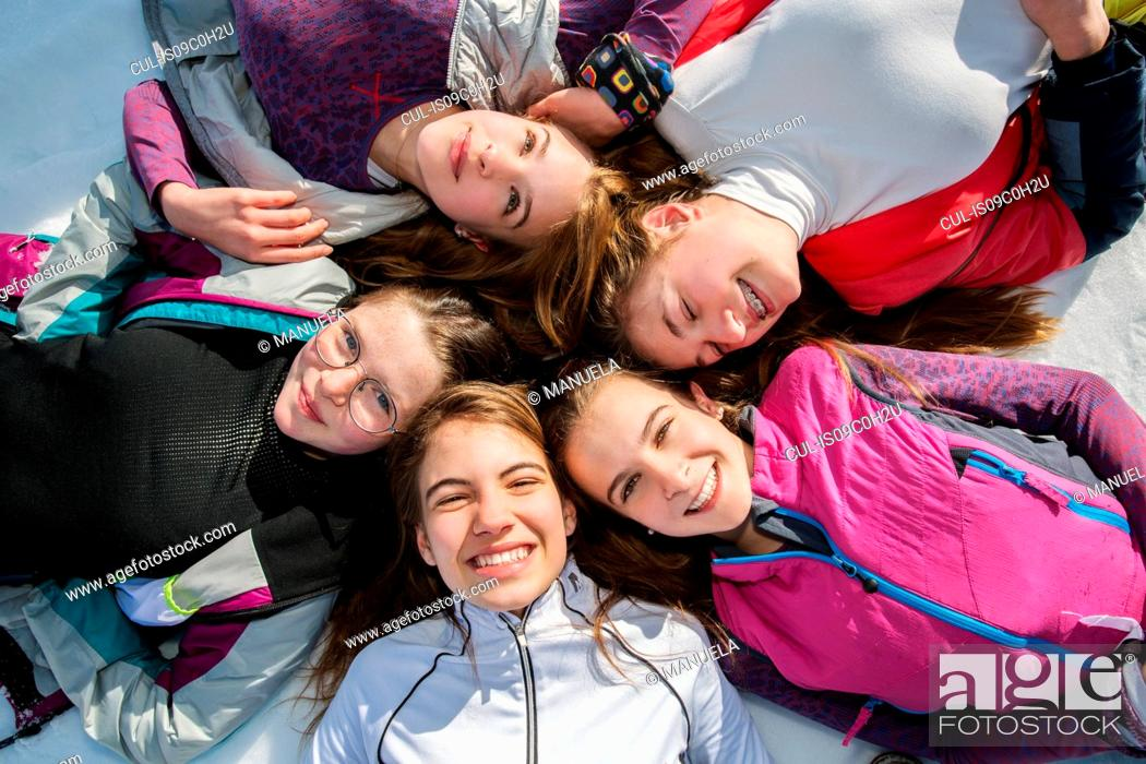 Stock Photo: Five teenage girl skiers lying in a circle in snow, overhead portrait, Tyrol, Styria, Austria.