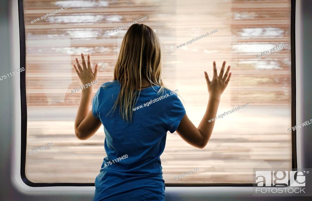 Stock Photo: Young girl looking through window, rear view.