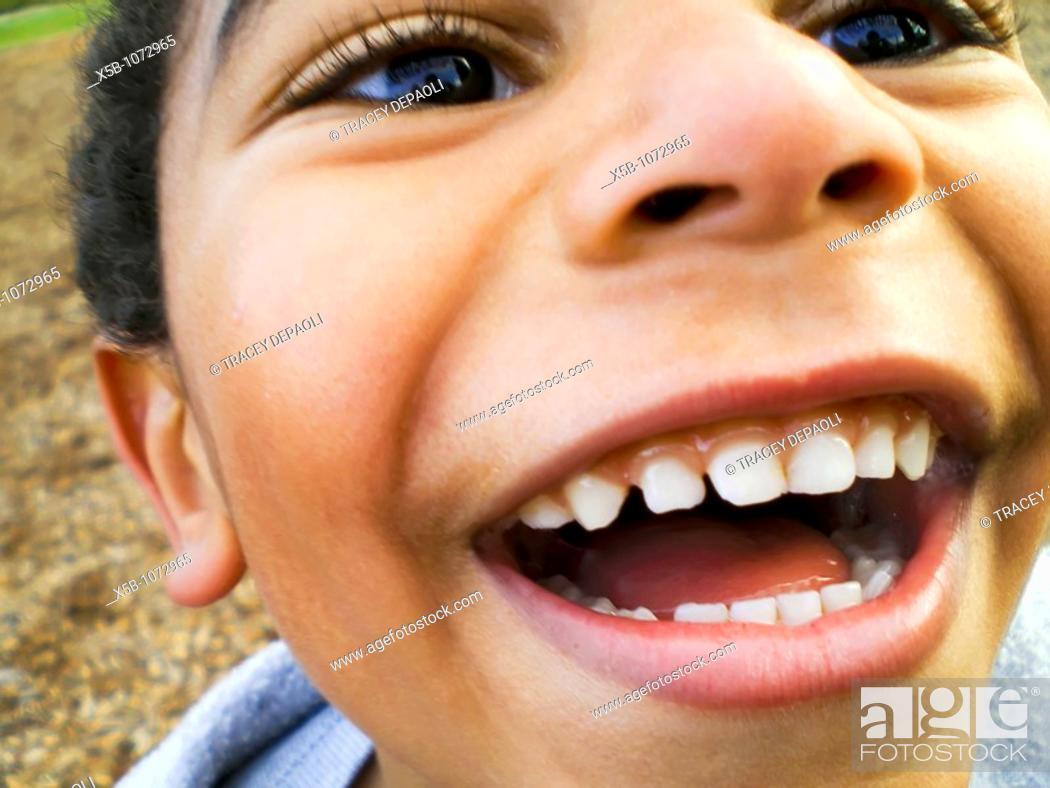 Stock Photo: young multiracial boy, laughing joyfully  close up, Horizontal.