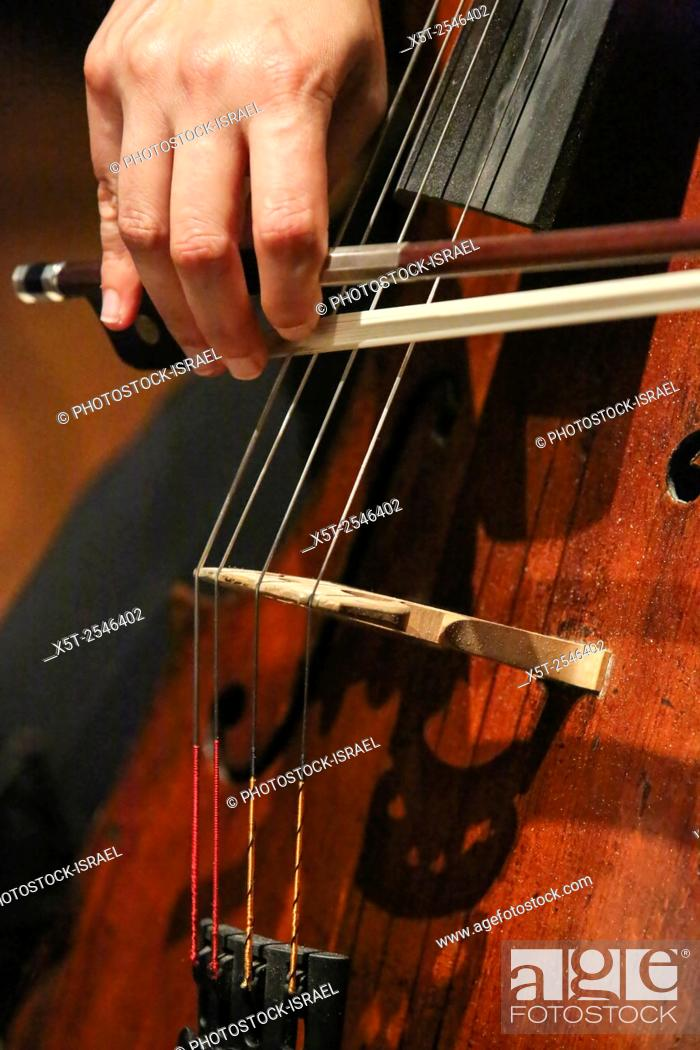 Stock Photo: Close up of the cellist's hands and bow while playing a cello.