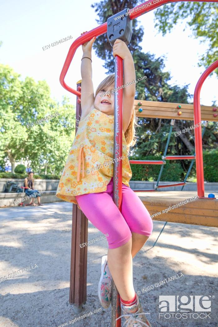 Stock Photo: Three years old blonde girl with yellow dress and pink tights playing hanging on monkey bars in outdoor playground, with mother woman watching.