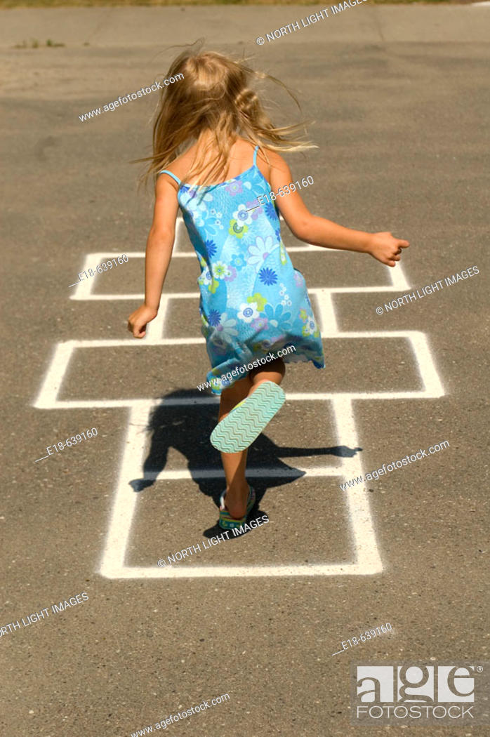 Stock Photo: Young girl, 4 years old, playing hopscotch in park.  White Rock, BC, Canada.  Near Vancouver.