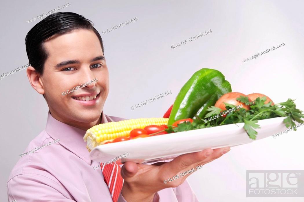 Stock Photo: Businessman holding a platter of fresh vegetables.