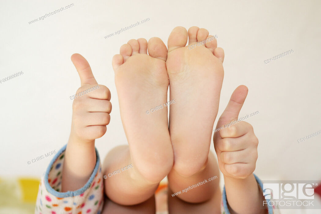 Stock Photo Girl Showing Soles Of Her Feet And Hands With Thumbs Up